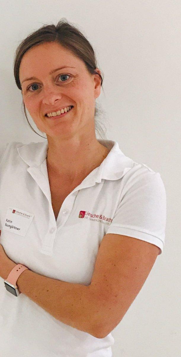 Die aus Bad Schönborn stammende Katrin Baumgärtner steht vor einem weißen Hintergrund. Sie hat ihre braunen Haare zu einem Zopf gebunden und trägt ein weißes Liebscher & Bracht T-Shirt. Sie lacht in die Kamera und hält einen Arm vor den Brustkorb.