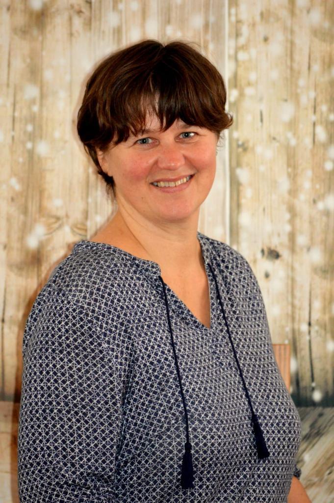 Das Foto zeigt Katrin Hartmann aus Beetzsee vor einem erleuchteten hellen braunen Hintergrund. Sie hat kurze braune Haare und trägt eine blau-weiße Bluse an.