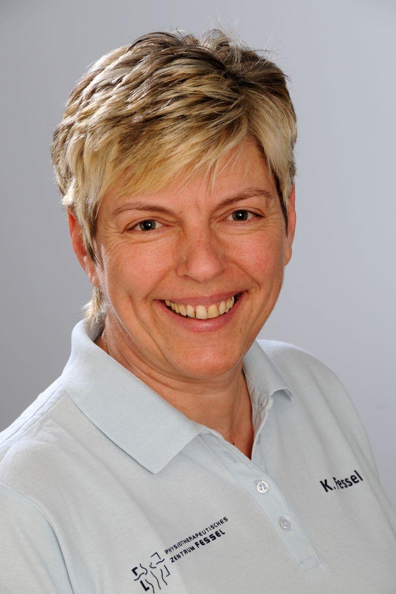 Das Foto zeigt Kerstin Fessel vor einem weißen Hintergrund. Sie hat kurze blonde Haare und lacht in die Kamera. Sie trägt ein weißes Polo T-Shirt mit dem Logo der Praxis.