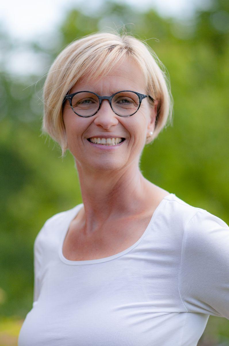 Auf dem Foto ist Kerstin Mund aus Mönchengladbach zu sehen. Der Hintergrund ist grün und hell. Sie hat kinnlange blonde Haare und eine dunkle runde Brille und trägt ein weißes Shirt.