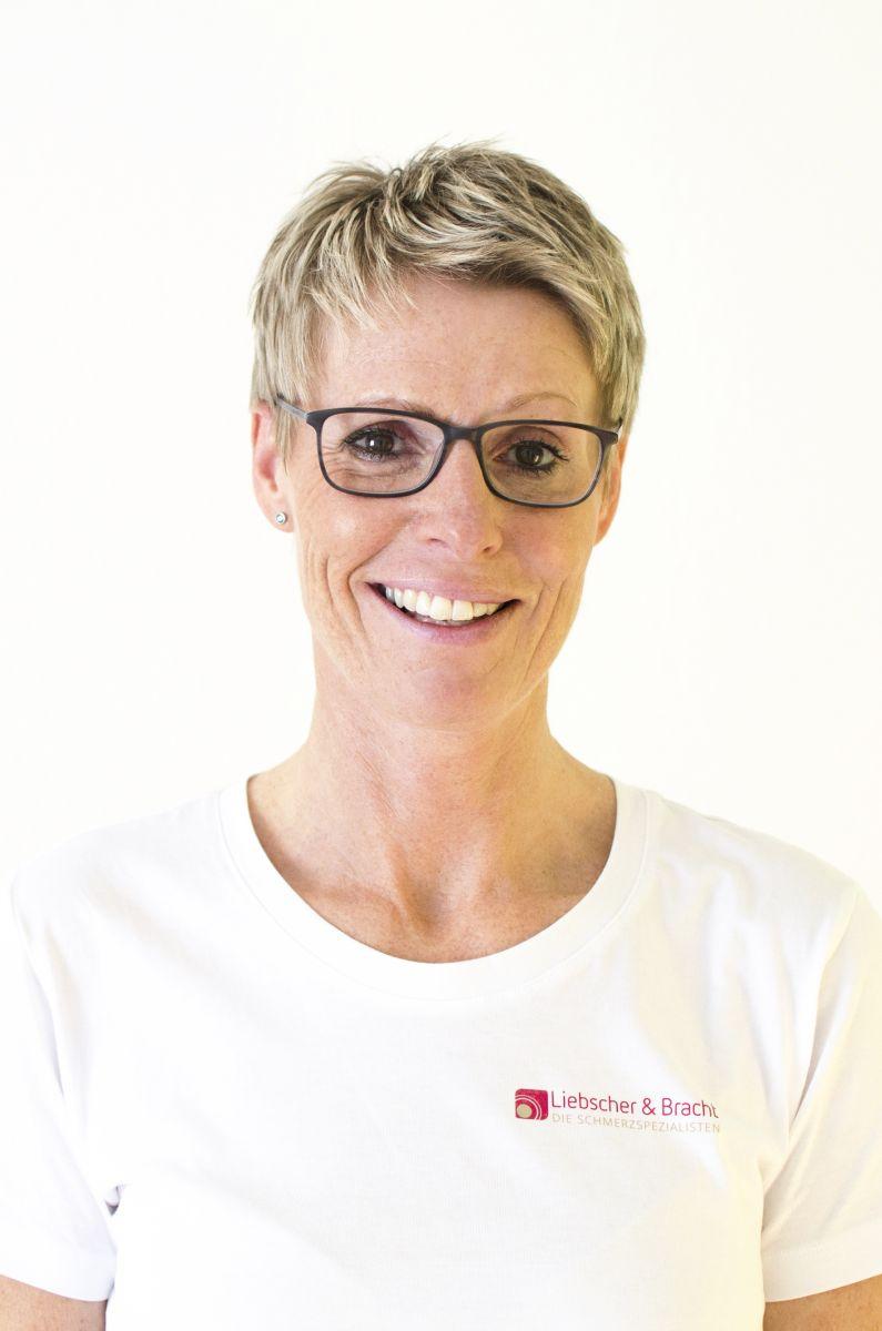 Das Foto zeigt die Physiotherapeutin Kirsten Zech aus Niestetal. Sie steht vor einem hellen Hintergrund und hat kurze blonde Haare. Sie hat eine dunkle eckige Brille und trägt ein weißes Liebscher & Bracht T-Shirt.