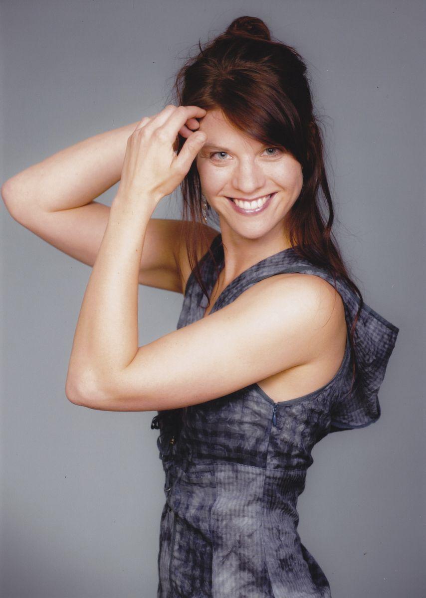 Auf dem Foto ist Kristina Glänzel vor einem grauen Hintergrund fotografiert. Sie steht seitlich zur Kamera und lacht in diese und hält ihre Hände an die Haare. Sie hat lange dunkelbraune Haare, die sie halb nach hinten gebunden hat und ein grau gemusterte