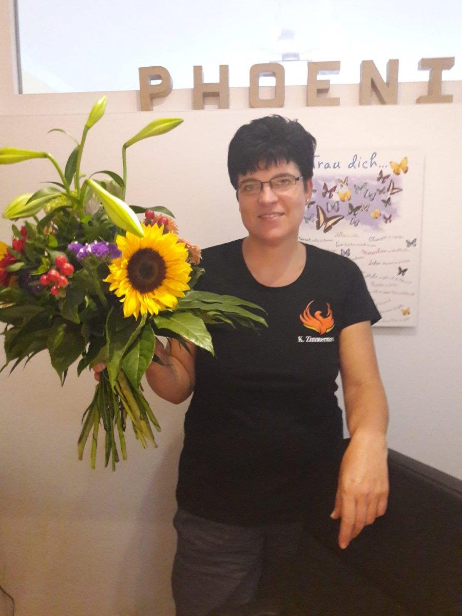 Das Foto zeigt Kirsztina Zimmermann aus Lutherstadt Wittenberg vor einem hellen Hintergrund. Sie hält einen großen Blumenstrauß mit einer Sonnenblume in der Hand. Auf dem Foto hat sie kurze schwarze Haare und trägt ein schwarzes T-Shirt mit Aufdruck.