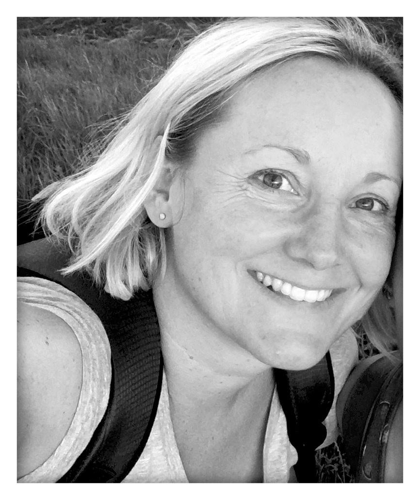 """Auf dem schwarz-weiß Foto ist Manuela Schmidt abgebildet. Sie lacht in die Kamera und hat kinnlange helle Haare. Sie trägt einen Rucksack und ein T-Shirt. Auf dem Foto ist unten rechts ein Button mit dem Slogan """"Schmerzfrei On Tour"""" eingeblendet."""