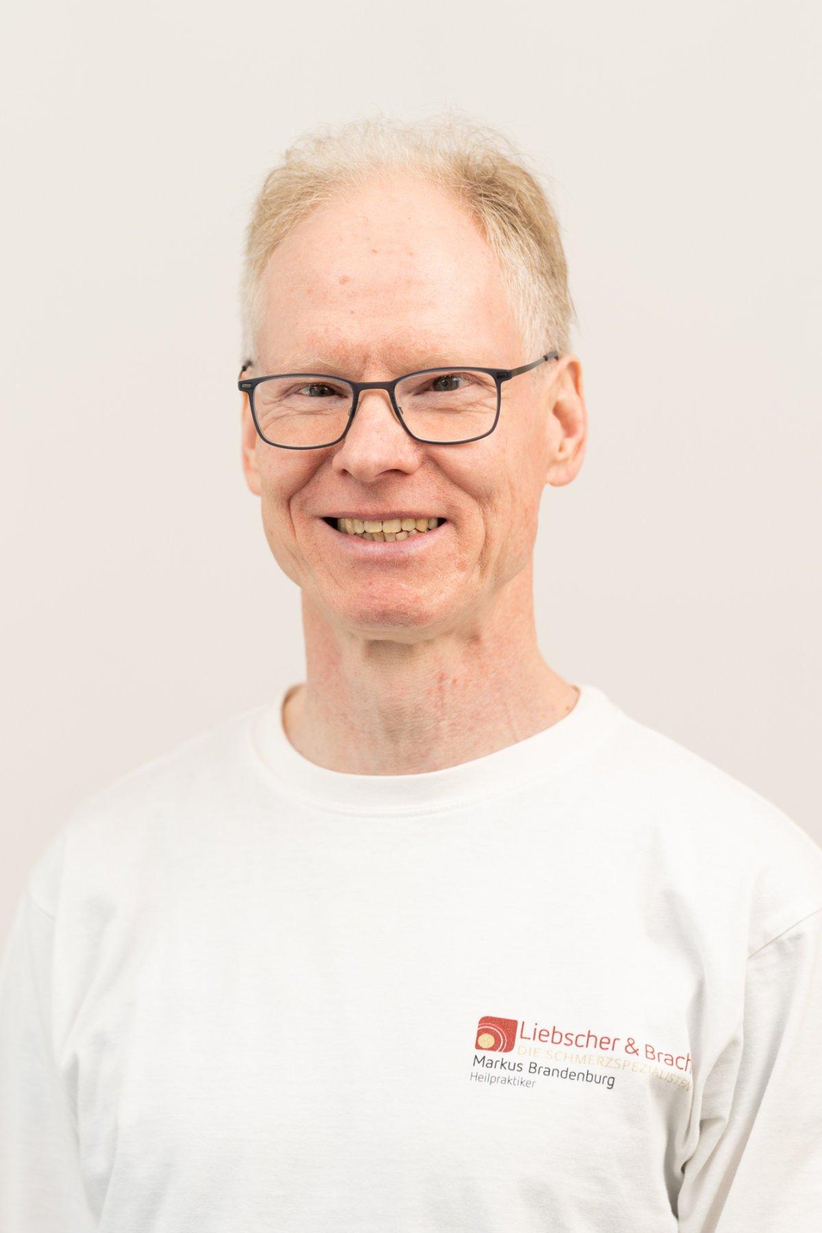 Der Heilpraktiker aus Berlin Steglitz Markus Brandenburg steht vor einem weißen Hintergrund. Er trägt ein Liebscher & Bracht T-Shirt, eine schwarze eckige Brille und hat kurze blond-graue Haare.