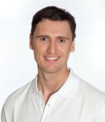 Das Portraitbild zeigt den Physiotherapeuten Markus Teichmann. Er hat braune Haare und trägt ein weißes Polo T-Shirt.