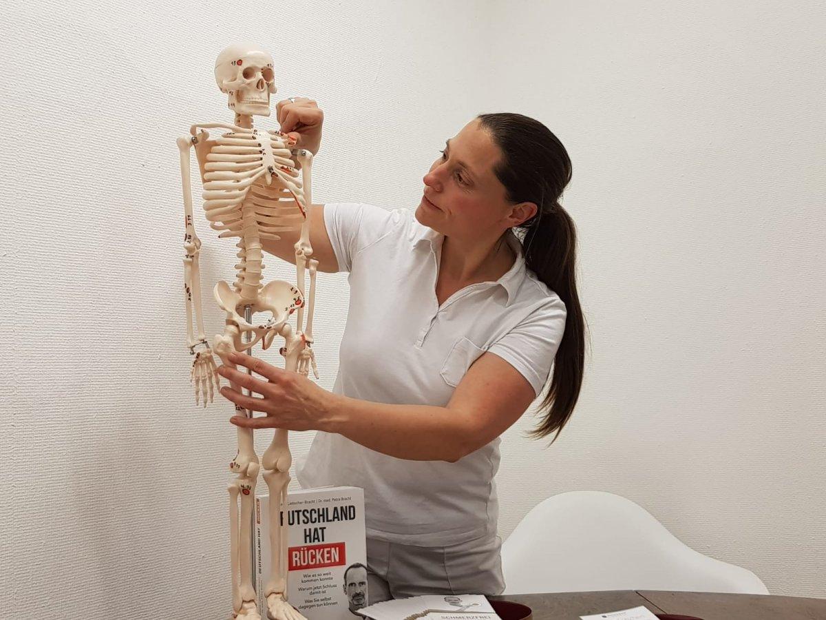 """Das Foto zeigt Martha Holzhausen, wie sie an einem Skelett etwas erklärt. Sie hat lange schwarze Haare, die sie als Zopf trägt. Dazu hat sie ein weißes Polo T-Shirt an. Neben dem Modellskelett steht das Buch """"Deutschland hat Rücken""""."""