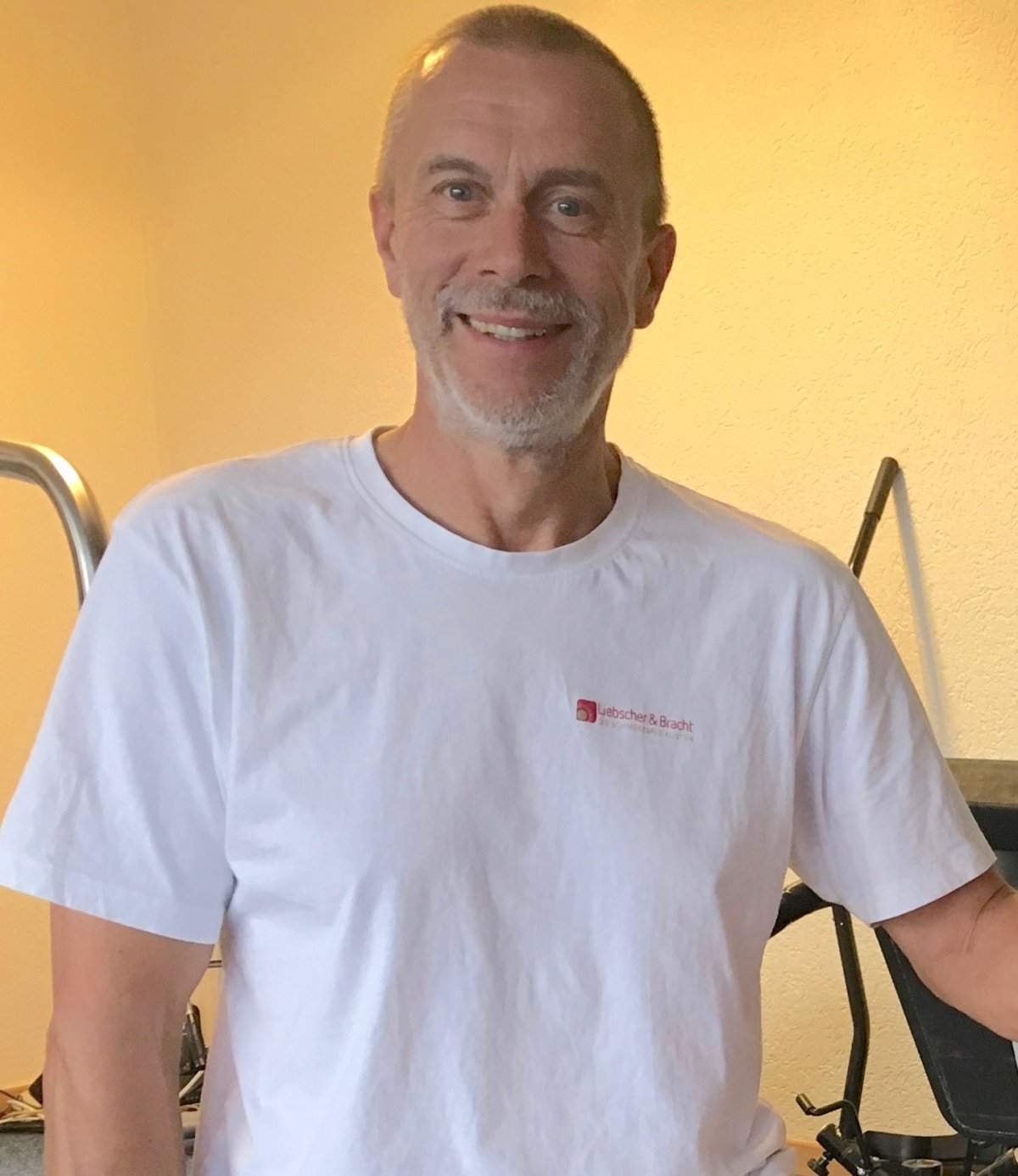 Physiotherapeut aus Wabern, Matthias Goering trägt ein weißes Liebscher & Bracht T-Shirt und steht vor einem gelben Hintergrund mit Fitnessgeräten.