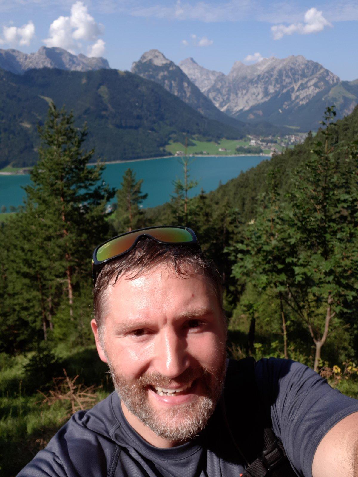 Auf dem Foto ist Matthias Schmieder zu sehen. Im Hintergrund sind ein See und Berge zu erkennen. Er hat kurze braune Haare und einen Vollbart. Auf dem Foto trägt er eine Sonnenbrille auf dem Kopf und ein graues T-Shirt.