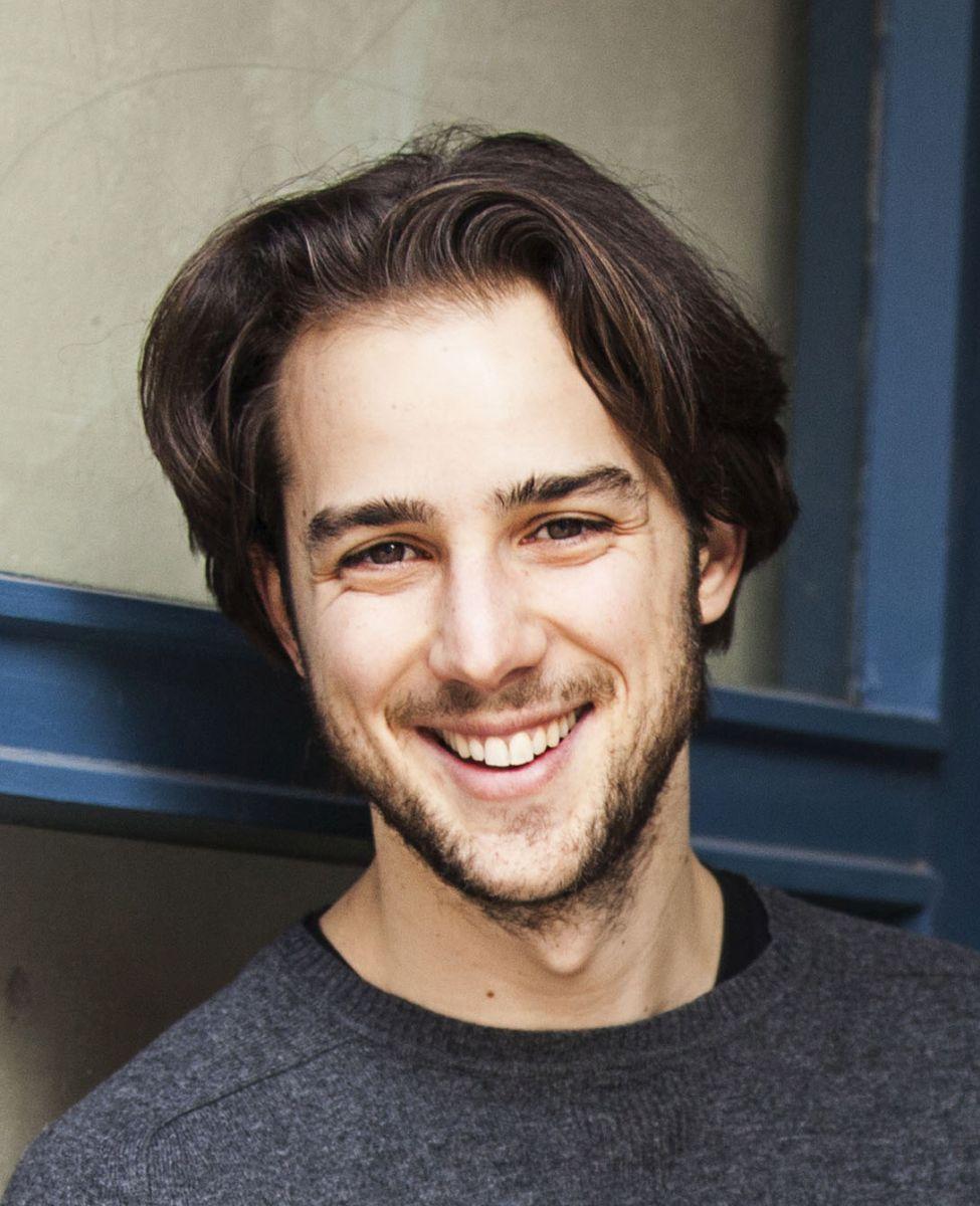 Maximilian Schön, Qualitätspartner Liebscher & Bracht, steht vor einer blau-grauen Tür. Das Portraitfoto zeigt ihn mit längeren braunen Haaren, Bart und einem dunkelgrauen Pullover.