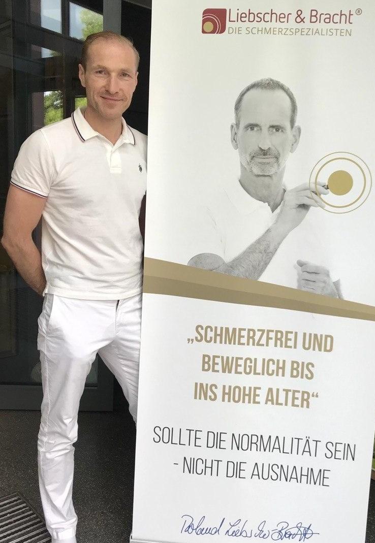 Das Portraitfoto zeigt Meik Schneider aus Siegen. Er hat kurze dunkelblonde Haare und trägt ein graues Hemd.