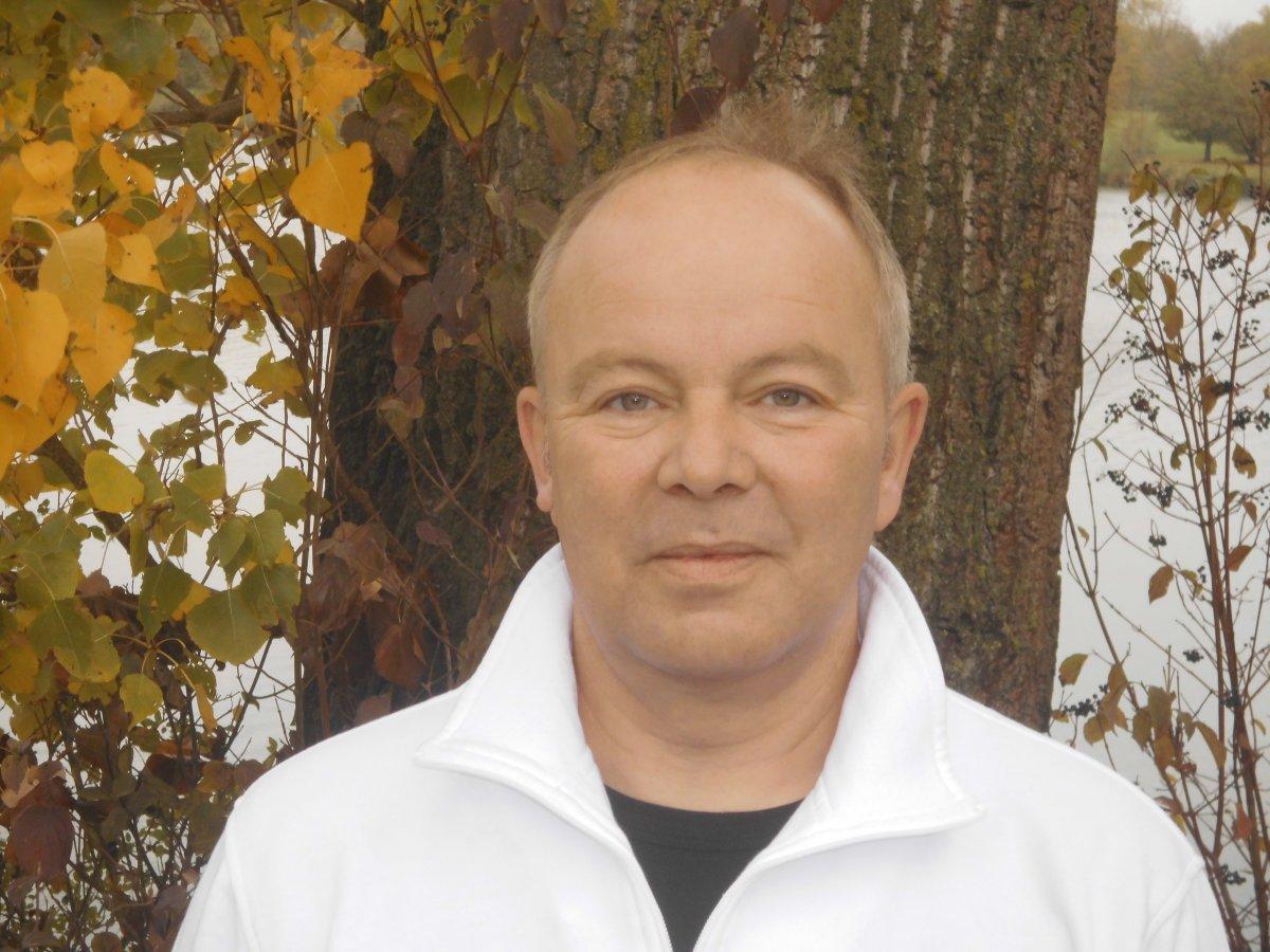Auf dem Foto ist Michael Fleischer aus Münster vor einem Baumstamm und Blättern zu sehen. Er hat kurze hellgraue Haare und eine Halbglatze. Er trägt einen weißen Pullover und ein schwarzes T-Shirt.