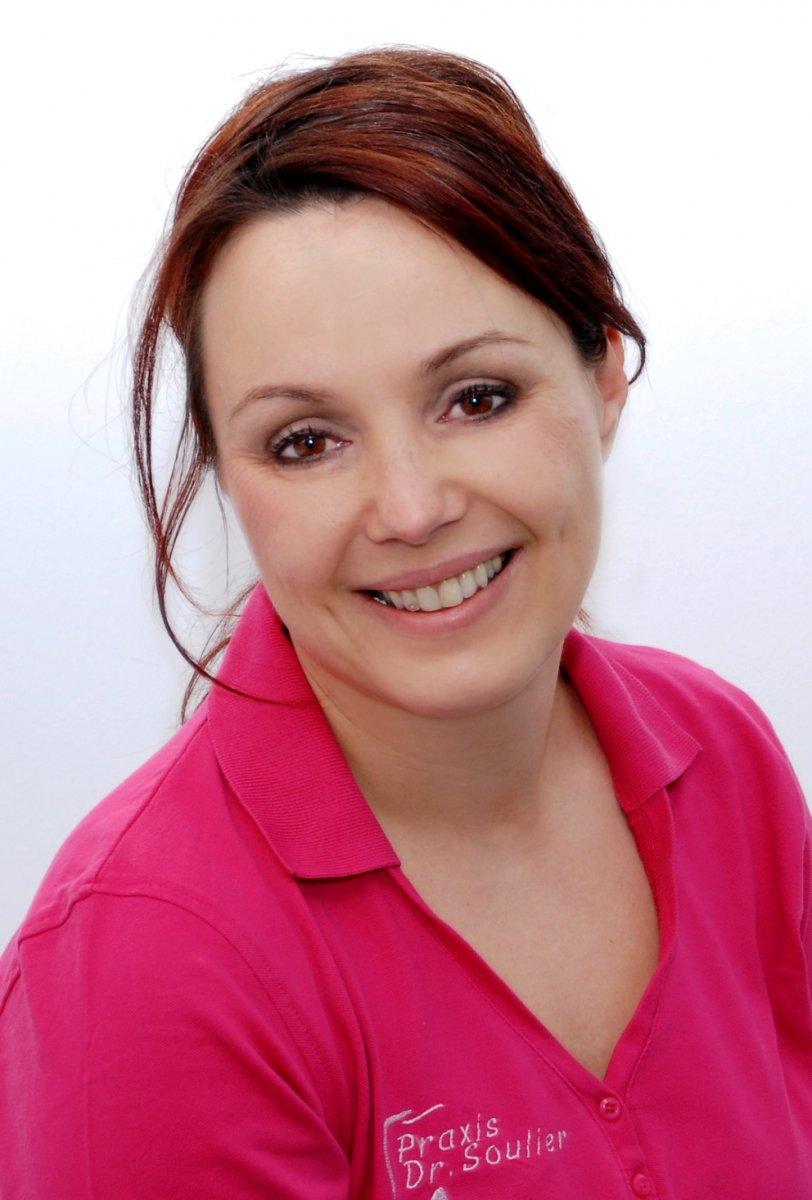 Heilpraktikerin Nicole Soulier sitzt lächelnd vor einem weißen Hintergrund. Sie trägt ein pinkes Polo T-Shirt und hat dunkelrote Haare, welche als Zopf gebunden sind.