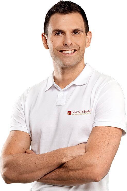 Der Schmerzspezialist und Bewegungstherapeut nach Liebscher & Bracht steht lächelnd vor einem weißen Hintergrund. Patrick Wentzel trägt ein weißes Liebscher & Bracht Polo T-Shirt und hat kurze braune Haare.