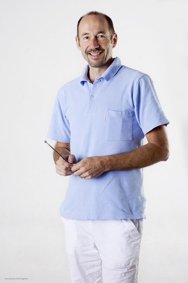 Auf dem Foto steht der Schmerztherapeut Peter Herndler vor einem weißen Hintergrund. Er hat kurze braune Haare und eine Halbglatze sowie einen Dreitagebart. Er trägt ein hellblaues Polo T-Shirt und eine weiße Hose.