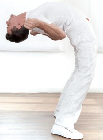 Das Foto zeigt Peter Schneider aus Homburg bei einer Dehnübung. Er hat kurze braune Haare und trägt weiße Kleidung. Auf dem Foto dehnt er seinen Rücken weit nach hinten, sodass dieser fast waagerecht ist und hält die Arme neben den Kopf.