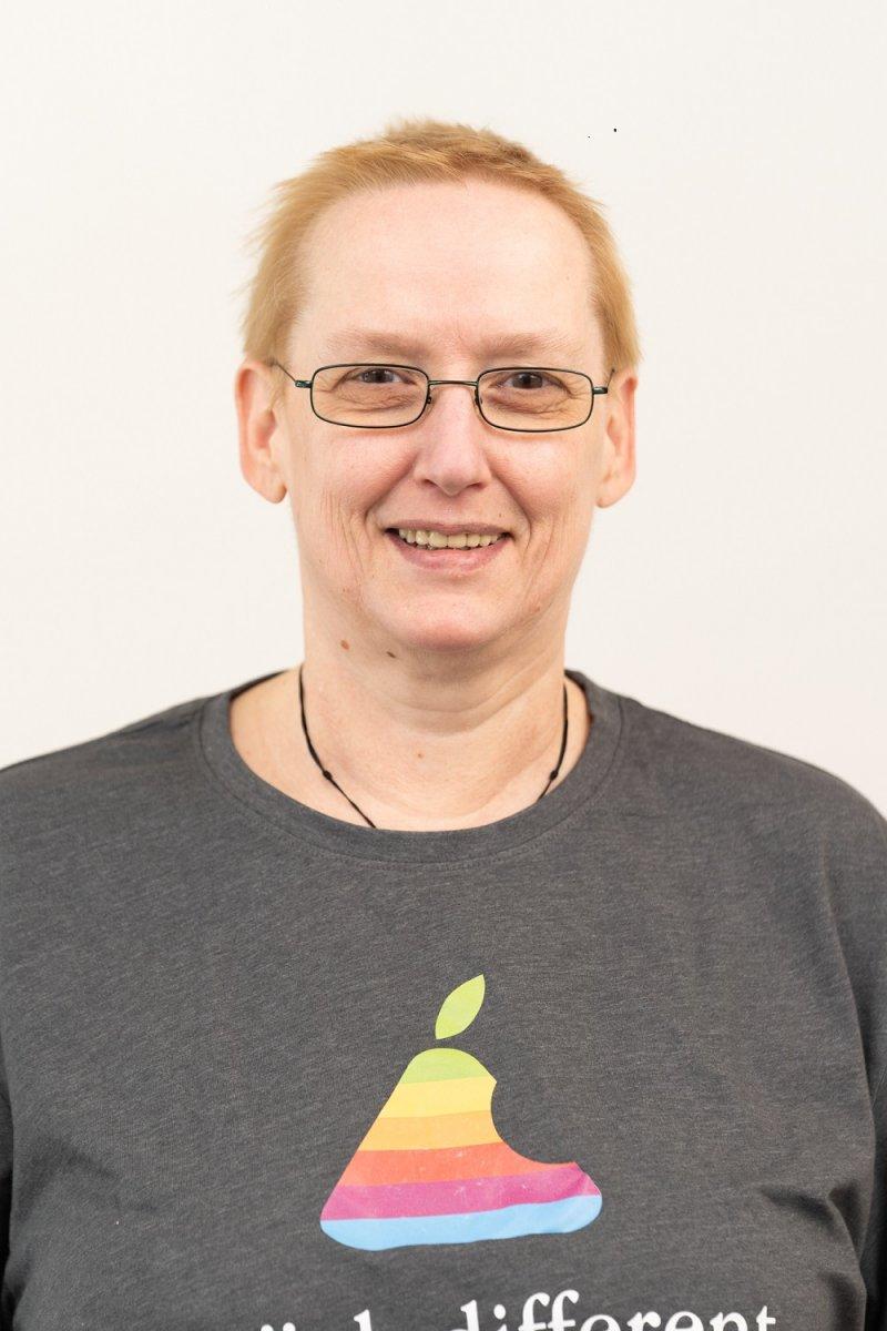 Die Heilpraktikerin Petra Butschko aus Berlin Charlottenburg steht vor einem hellen Hintergrund. Sie hat kurze hellrote Haare und trägt eine dunkle Brille und ein graues T-Shirt mit einem bunten Aufdruck.