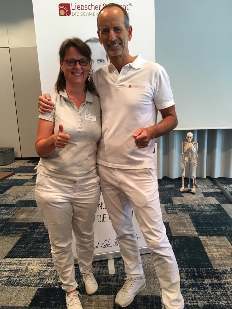 Auf dem Foto steht Petra Fietze-Jank neben Roland Liebscher-Bracht. Beide halten einen Daumen nach oben und tragen weiße Kleidung. Petra Fietze-Jank hat schulterlange braune Haare und einen geraden Pony sowie eine eckige dunkle Brille.