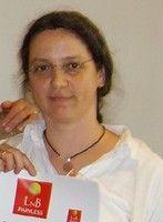 Das Foto zeigt Riek Rohland aus Kaiserslautern. Sie trägt ihre langen braunen Haare als Zopf und eine randlose Brille. Dazu ein weißes Polo T-Shirt und eine schwarze Kette. Am unteren Bildrand hält sie Ihre Urkunde der L&B Ausbildung hoch.
