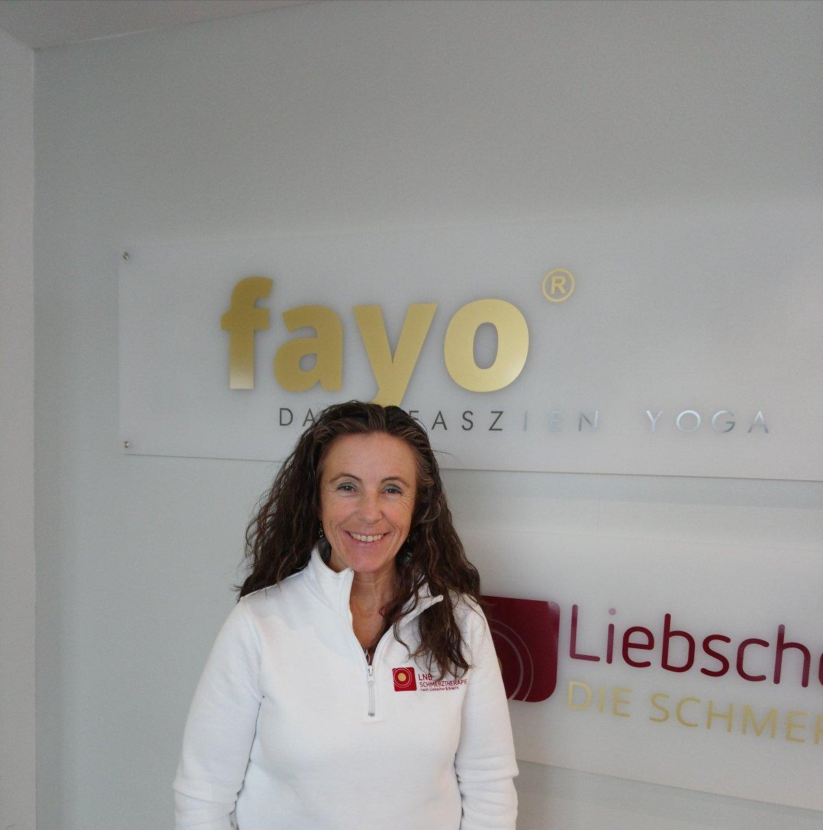Das Foto zeigt Rita Harlos aus 56242 Selters. Sie hat lange braune Haare, die sich leicht locken. Auf dem Foto steht sie vor einem FAYO und Liebscher & Bracht Schild und trägt einen weißen Pullover.