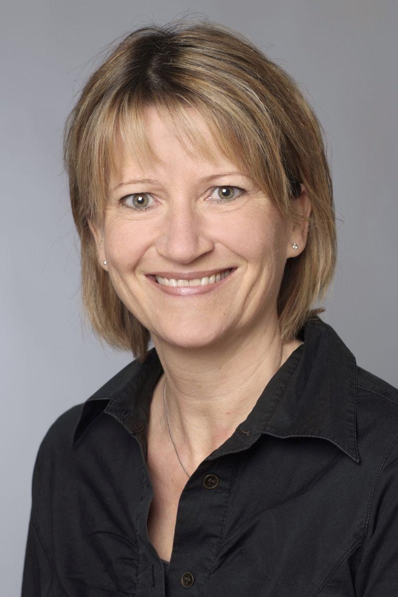 Das Portraitfoto der Schmerztherapeutin Britgitte Rüegsegger zeigt sie vor einem grauen Hintergrund. Sie hat halblange blond-braune Haare und trägt eine schwarze Bluse.