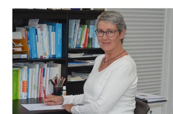 Das Foto zeigt Sabine Henning aus 24536 Neumünster. Sie sitzt an einem Schreibtisch und im Hintergrund ist ein Bücherregal zu sehen. Sie hat kurze dunkelgraue Haare und trägt eine eckige Brille sowie ein weißes Shirt.