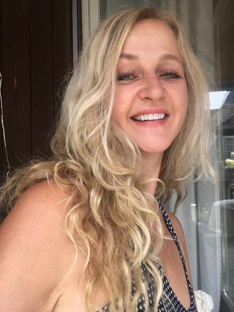 Sandra Lattmann aus Solothurn ist von der Seite fotografiert. Im Hintergrund ist eine Scheibe zu sehen. Sie hat langes blondes lockiges Haar und trägt auf dem Foto ein schwarz-weiß gepunktetes Top.
