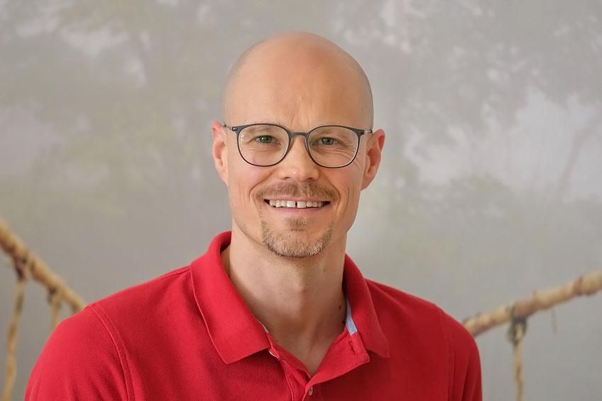 Das Foto zeigt den Heilpraktiker für Physiotherapie Sergej Rempel in einem Behandlungsraum. Er trägt eine schwarze randlose Brille und ein weißes Polo T-Shirt mit schwarzen Rändern.