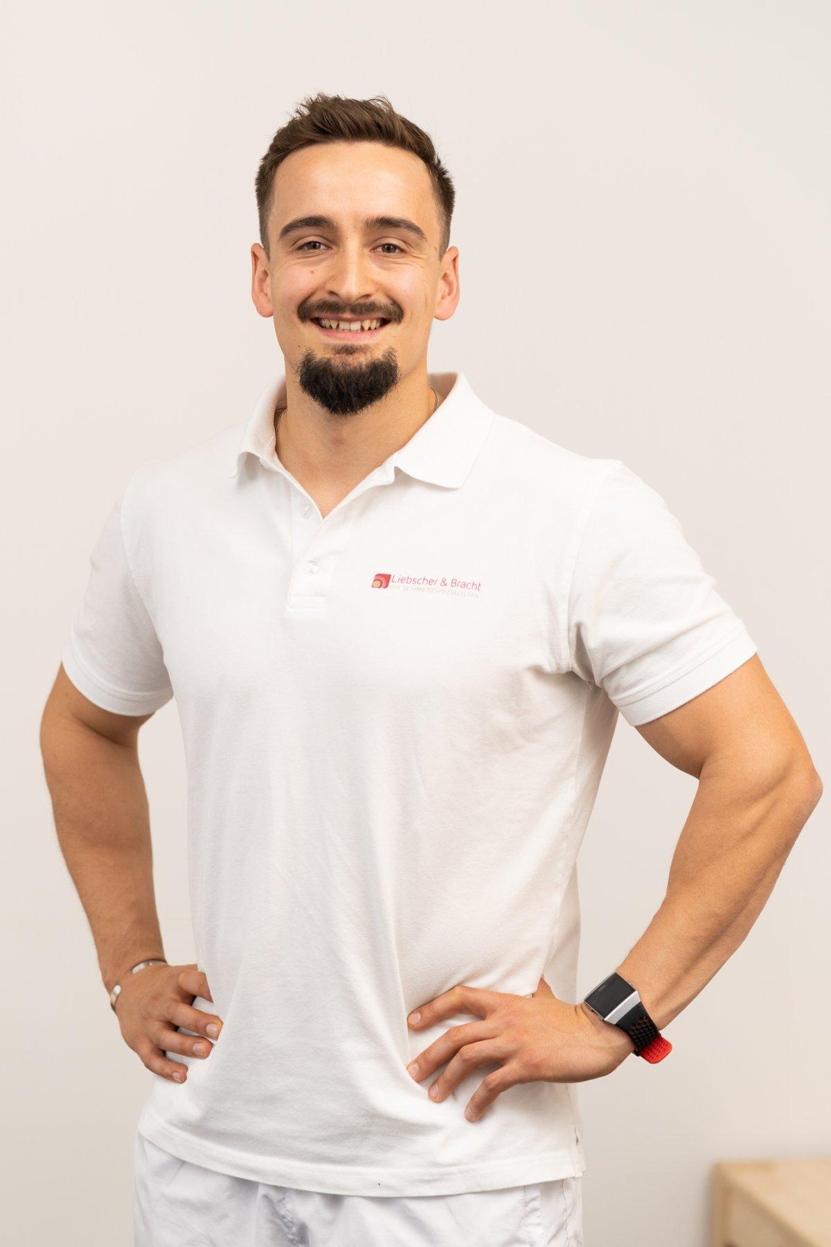 Auf dem Foto steht der sympathische, sportliche Simon Bösch vor einem weißen Hintergrund. Er trägt weiße Kleidung und ein Liebscher & Bracht T-Shirt und hat kurze braune Haare und einen Bart.