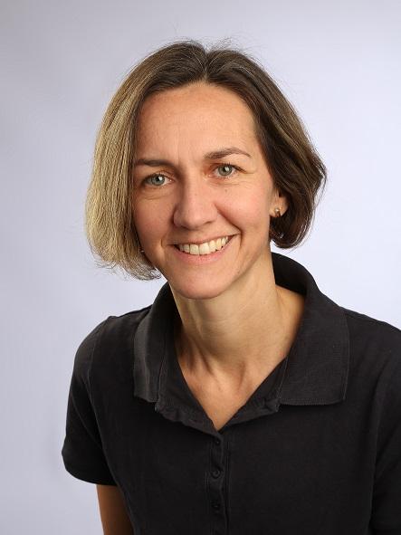 Das Portraitfoto zeigt die Physiotherapeutin Simone Aigle aus Blaustein. Sie steht vor einem hellgrauen Hintergrund. Ihre braunen Haare sind Kinn lang und dazu trägt sie ein schwarzes Polo T-Shirt.