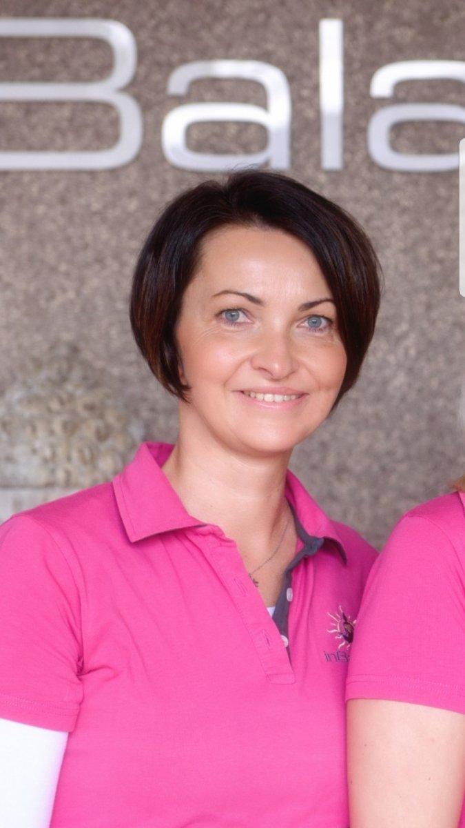 Vor einem grauen Hintergrund ist Sonja Neuhaus aus Hamm fotografiert. Sie hat kinnlange braune Haare, trägt eine weiße kurzärmlige Bluse und schaut lächelnd in die Kamera.