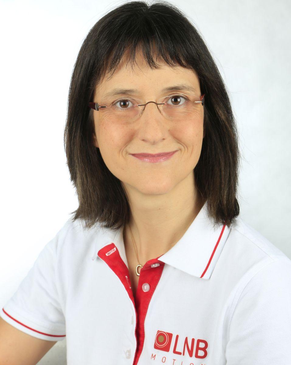 Das Foto zeigt Susanne Carl-Schröder vor einem weißen Hintergrund. Sie hat schulterlange braune Haare und einen geraden Pony. Sie trägt eine randlose Brille und ein weißes Liebscher & Bracht Polo T-Shirt.
