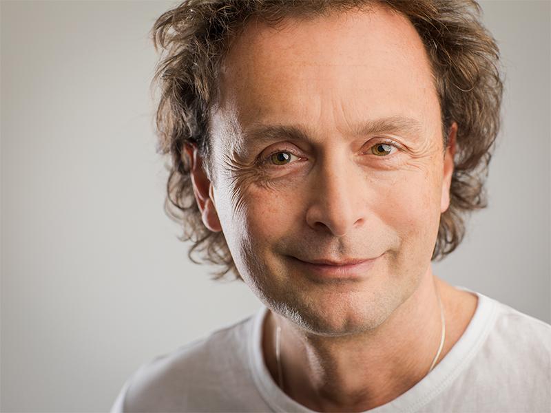 Das Foto zeigt Sven Sören Schumann aus Oberursel im Taunus. Er hat kurze braune Haare, die sich locken und lächelt in die Kamera. Der Heilpraktiker trägt ein weißes T-Shirt.