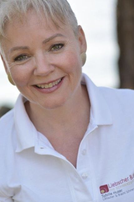 Die Liebscher & Bracht Schmerztherapeutin Sybille Huser ist in einem weißen Polo T-Shirt von Liebscher & Bracht fotografiert. Sie hat kurz blonde Haare.