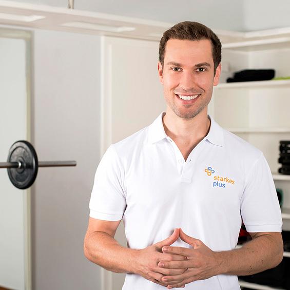 Der Heilpraktiker Tobias Seiler aus Stuttgart steht sympathisch vor dem Hintergrund eines hellen Raumes mit Trainingsgeräten. Er hat kurze braune Haare und trägt ein weißes Polo T-Shirt mit Aufschrift.