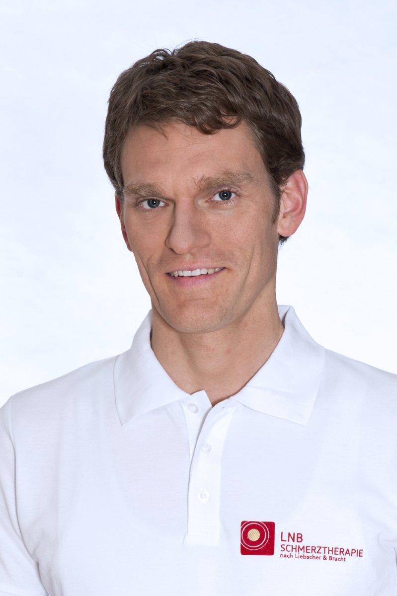 Auf dem Foto ist Ulli Betting aus Köln vor einer dunklen Steinwand zu sehen. Er hat dunkelblondes Haar und trägt ein Jeanshemd und lächelt in die Kamera.