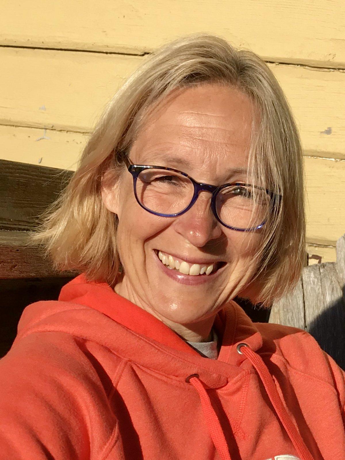 Auf dem Foto scheint Verena Knöffel die Sonne ins Gesicht. Sie lacht in die Kamera. Sie hat kinnlange blonde Haare und trägt eine eckige dunkle Brille sowie einen roten Kapuzenpullover.