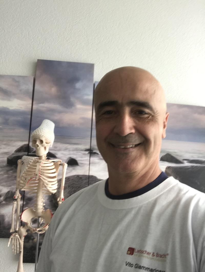 Auf dem Foto ist Vito Giammarinaro aus Buchs zu sehen. Im Hintergrund ist ein Meeresbild und ein Modellskelett zu sehen. Er hat eine Glatze und trägt ein weißes T-Shirt.