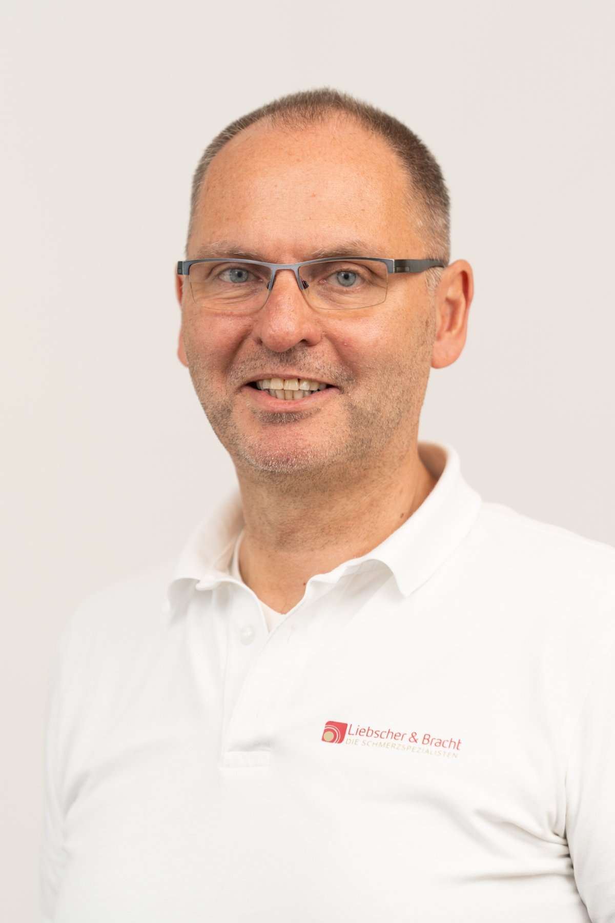 Das Foto zeigt den Heilpraktiker Jörg Kilian aus Illingen. Er wurde vor einem weißen Hintergrund fotografiert und trägt eine halbrandlose Brille sowie ein weißes Liebscher & Bracht Polo Shirt.
