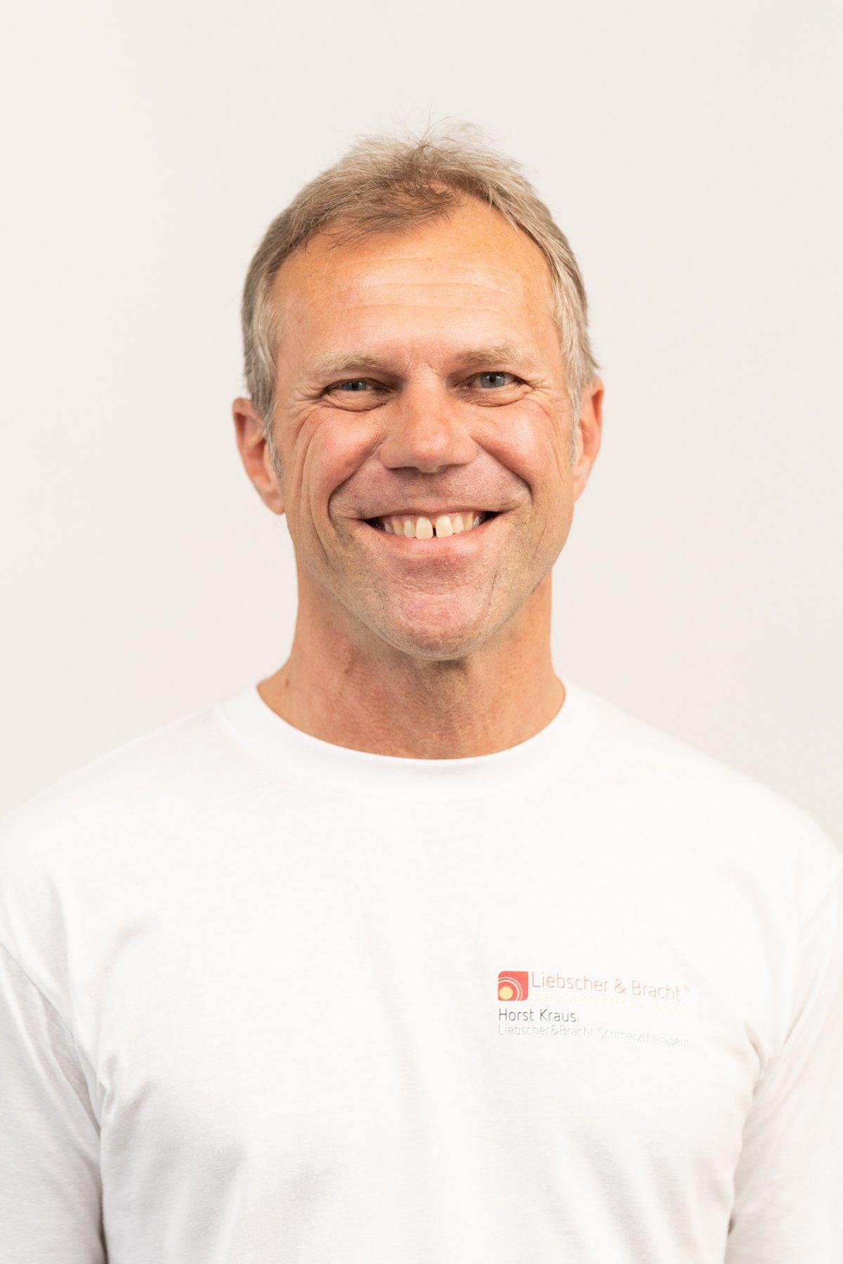 Horst Kraus, Heilpraktiker und Schmerztherapeut aus Forchheim, steht vor einem weißen Hintergrund. Er hat kurze graue Haare und trägt ein Liebscher & Bracht T-Shirt.