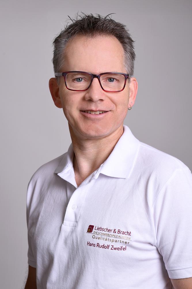 Das Portraitfoto von Hans Rudolf Zweifel zeigt ihn vor einem weißen Hintergrund und einem weißen Liebscher & Bracht Polo T-Shirt. Er hat kurze graue Haare und trägt eine dunkle eckige Brille.