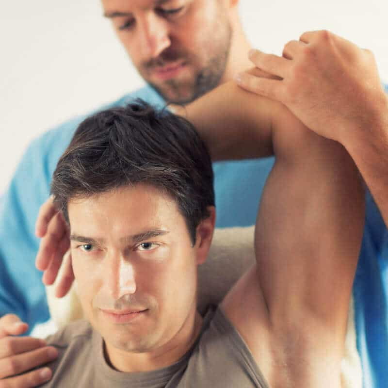 A therapist is treating the arm of a person.