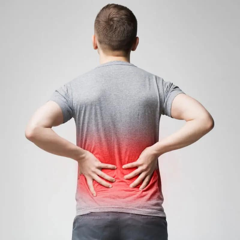 A man gripping his lower back in pain.