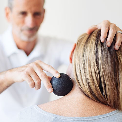 Roland Liebscher-Bracht treating a patient's neck with a massage ball.