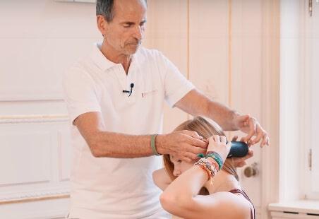 Roland Liebscher-Bracht helps a girl roll her neck with a foam roller.