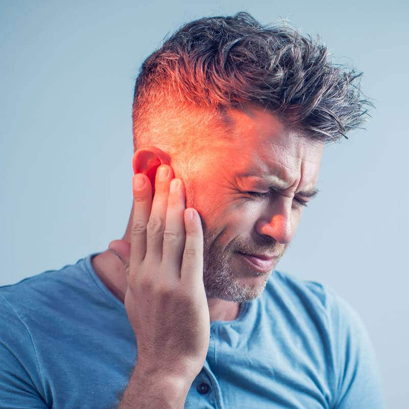 Man touching his ear and jaw in pain.