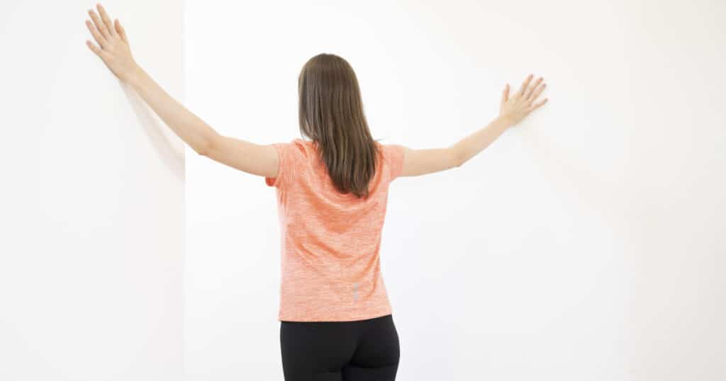 A woman is leaning against a wall with her arms up high to stretch her shoulder