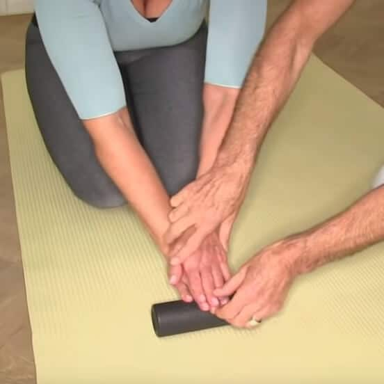 A woman is using a foam roller to treat her fingers.