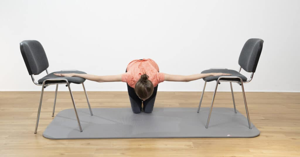 A woman is stretching her chest and shoulders by placing both her palms on chairs to get into a stretch for the uppder body