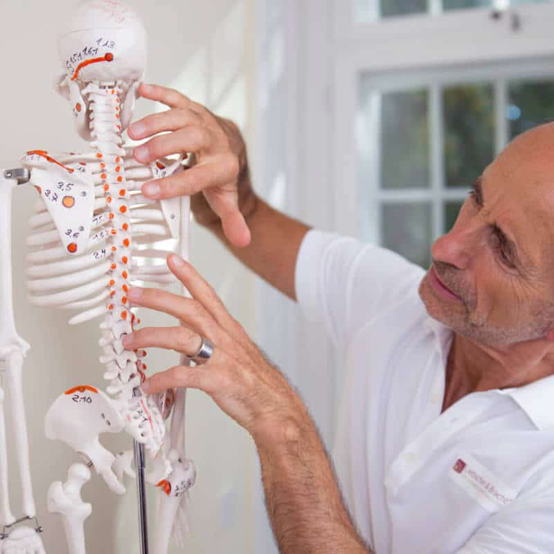 Roland Liebscher-Bracht is looking at the osteopressure points marked on a skeleton.